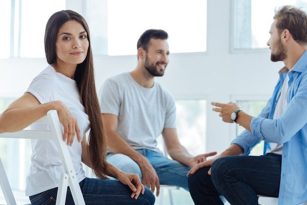Bela e simpática jovem sentada na cadeira e olhando para você durante uma sessão psicológica