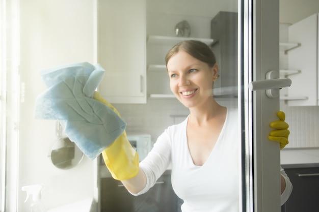 Bela e sorridente dona de casa nova que lava as janelas