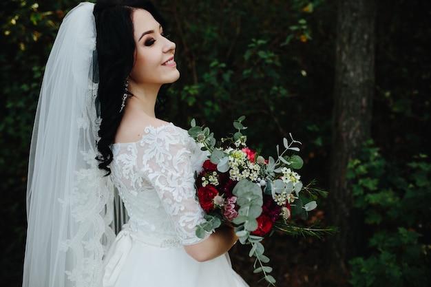 Bela e sorridente noiva segurando bouquet em pé lá fora