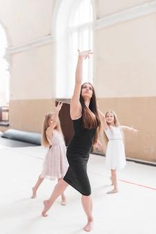 Bela elegante feminino dançando com duas garotas no estúdio de dança