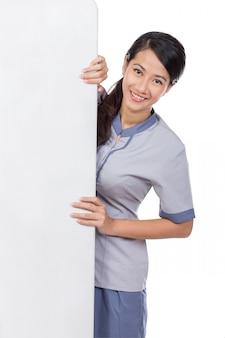 Bela empregada asiática de uniforme com quadro branco