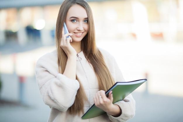 Bela empresária ao ar livre. jovem empresária sorridente usando smartphone moderno ao ar livre