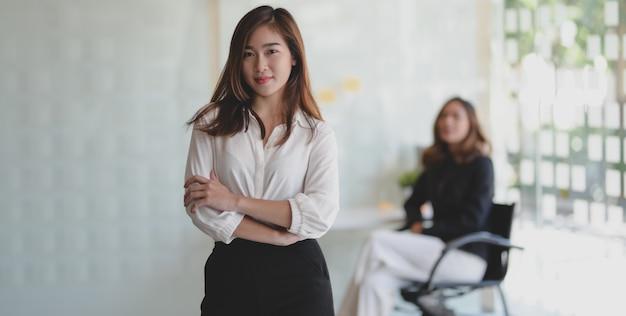 Bela empresária asiática em pé na sala de escritório e sorrindo para a câmera