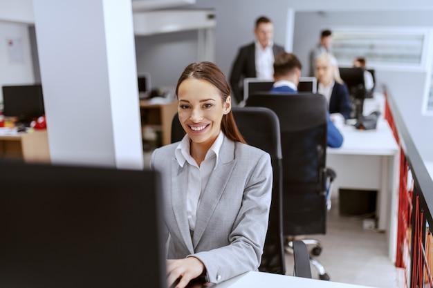 Bela empresária caucasiana positiva com roupa formal, sentado no escritório e usando o computador. mãos no teclado.