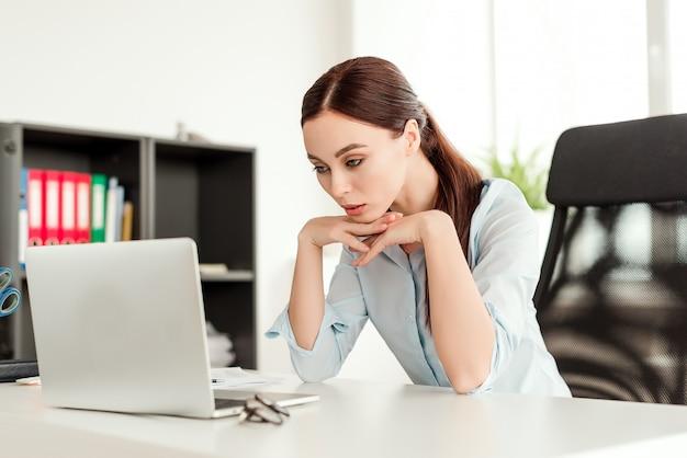 Bela empresária concentrada olhando para o laptop no seu local de trabalho no escritório