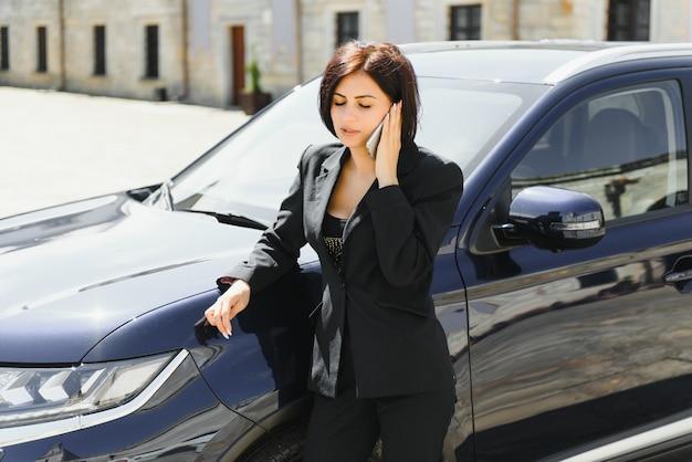 Bela empresária está falando no telefone celular e sorrindo em pé perto de seu carro e olhando para a frente com alegria