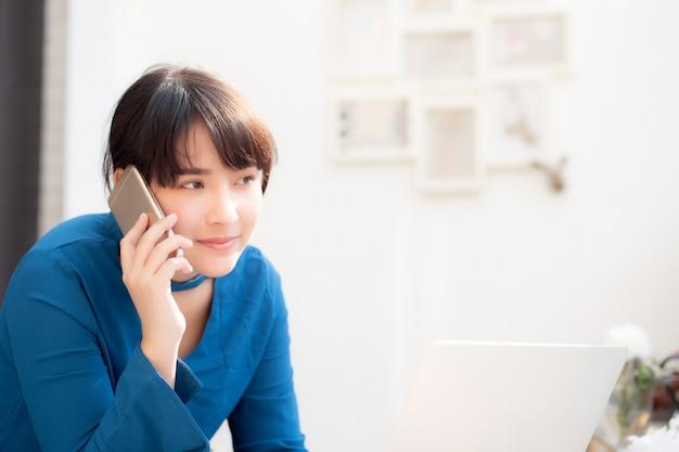 Bela empresária jovem asiática animado e contente de sucesso trabalhar com laptop