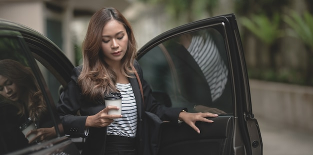 Bela empresária saindo do carro de luxo, segurando uma xícara de café
