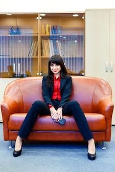 Bela empresária sorridente em um terno sentado em um escritório no sofá
