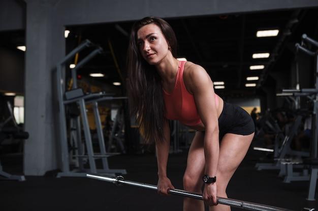 Bela esportista atlética se aquecendo na academia, levantando barra