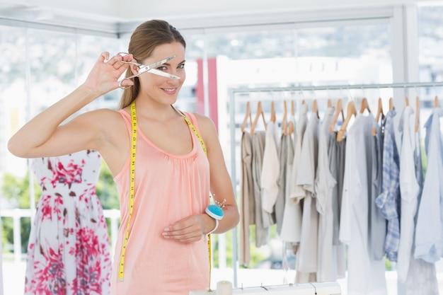 Bela estilista feminino que segura tesouras na loja