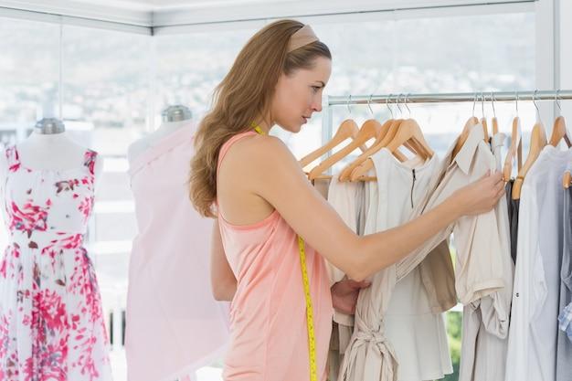 Bela estilista olhando roupas na cremalheira