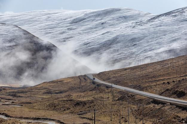 Bela estrada de inverno no tibete sob a montanha de neve, sichuan, china