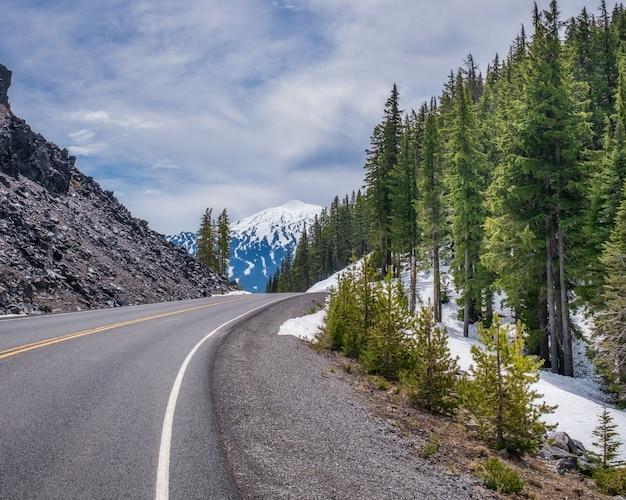 Bela estrada rochosa com neve ao lado de uma floresta