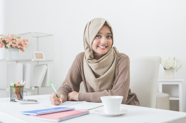 Bela estudante asiática com hijab fazendo lição de casa