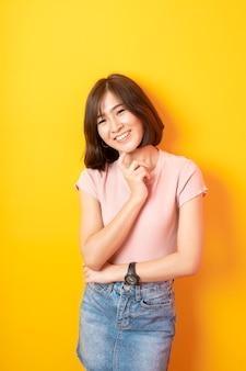 Bela estudante asiática feliz na parede amarela