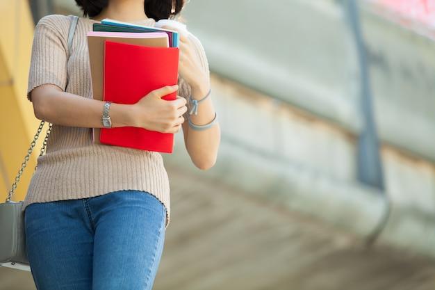 Bela estudante asiática feminino segurando seus livros e uma xícara de café