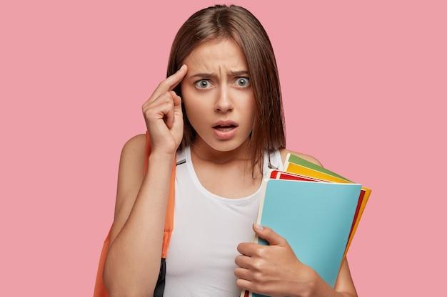 Bela estudante estressante posando contra a parede rosa