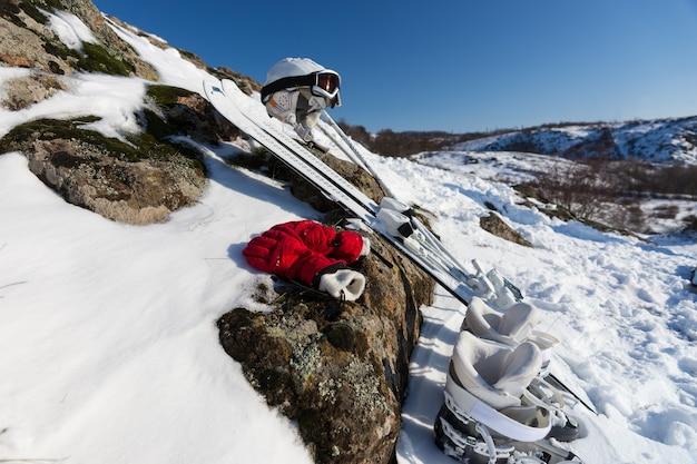 Bela exibição de botas brancas, par de esquis, capacete e luvas vermelhas colocadas em uma rocha coberta de neve sob o céu azul em um dia ensolarado de inverno