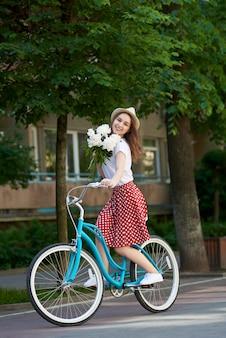 Bela fêmea na bicicleta retrô com peônias está andando junto
