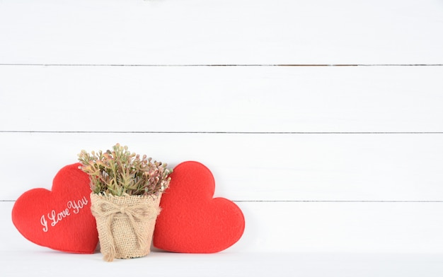 Bela flor marrom em um pote e coração vermelho sobre fundo branco de madeira