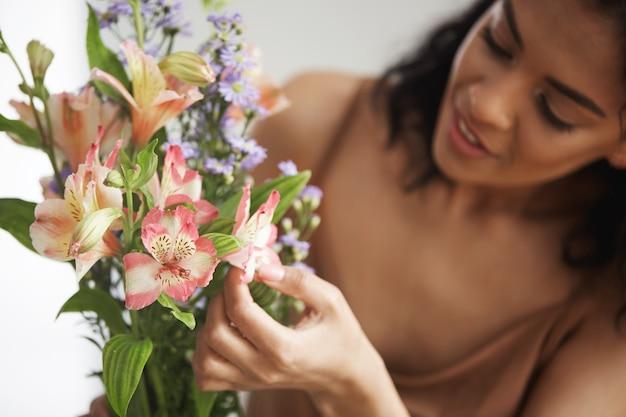 Bela florista feminina africana fazendo buquê de flores. concentre-se em alstroemerias.