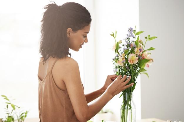 Bela florista feminina africana sorrindo fazendo buquê de flores.