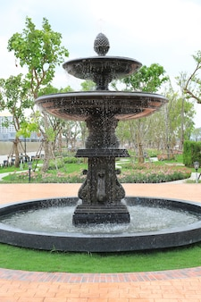 Bela fonte no jardim do parque. a água flui da fonte.