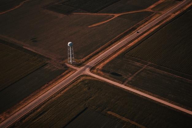 Bela foto aérea de cruzamento de estradas estreitas na zona rural com uma torre branca