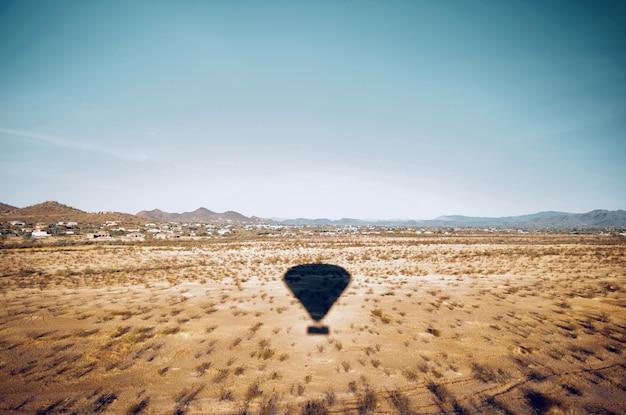 Bela foto aérea de um campo no deserto com a sombra de um balão de ar em movimento no céu