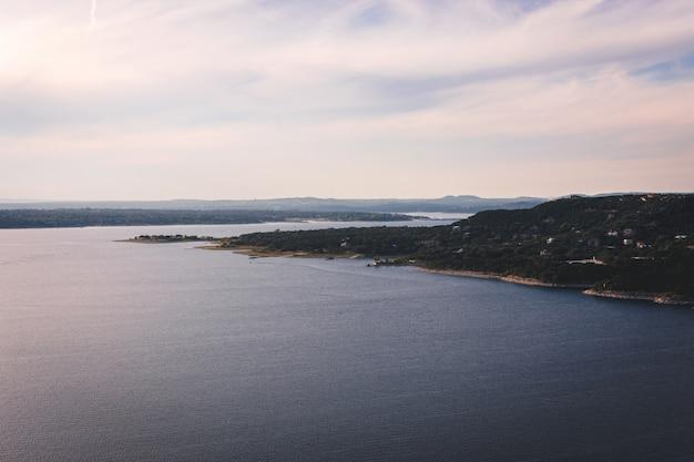 Bela foto aérea de um lago com um campo verde ao lado