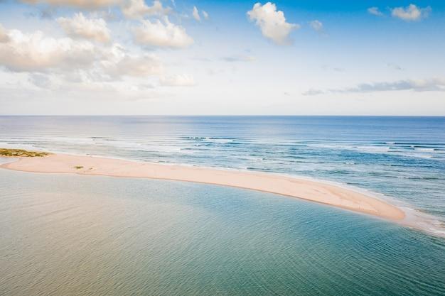 Bela foto aérea de um mar azul calmo com uma ilha no meio