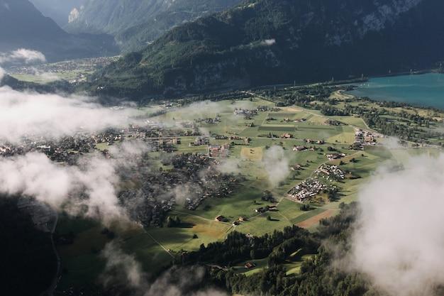 Bela foto aérea de uma cidade cercada por montanhas cobertas de nevoeiro