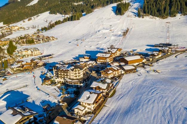 Bela foto aérea de uma cidade no topo de uma montanha nevada