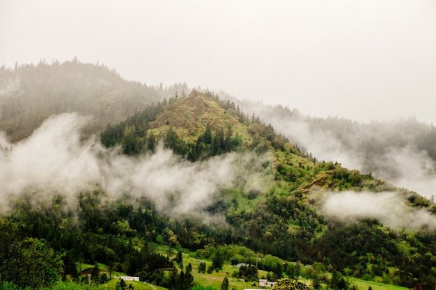 Bela foto aérea de uma montanha envolvida por nuvens