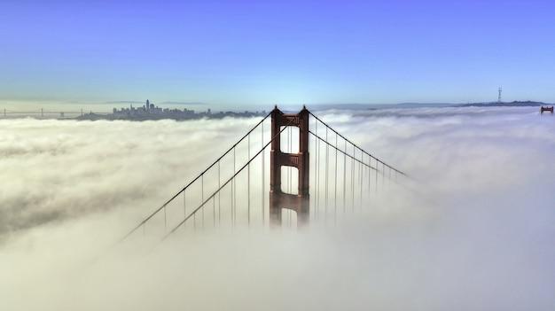 Bela foto aérea do topo de uma ponte cercada por nuvens e céu azul
