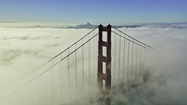 Bela foto aérea do topo de uma ponte rodeada por nuvens e céu azul