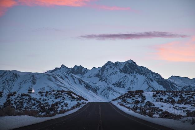 Bela foto ampla de uma estrada perto de montanhas cheias de neve sob um céu rosa e roxo