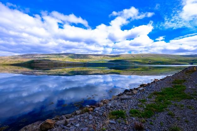Bela foto da água perto da costa rochosa e montanha à distância, com nuvens no céu