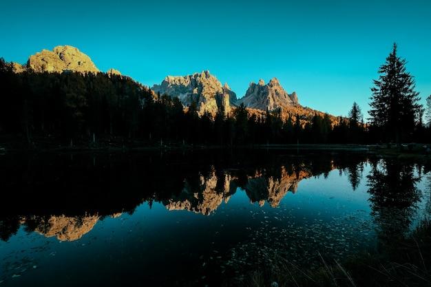 Bela foto da água refletindo as árvores e as montanhas com céu azul