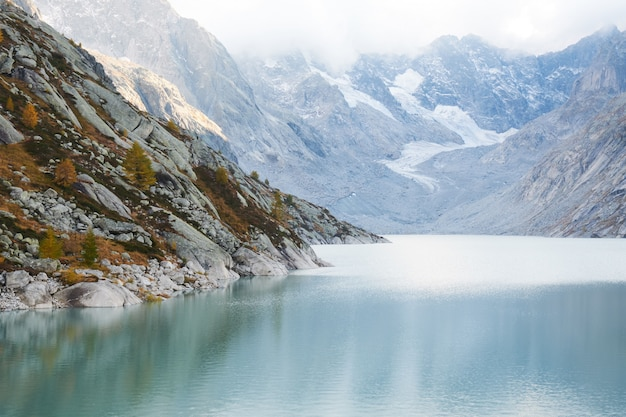 Bela foto da água rodeada por montanhas sob um céu nublado