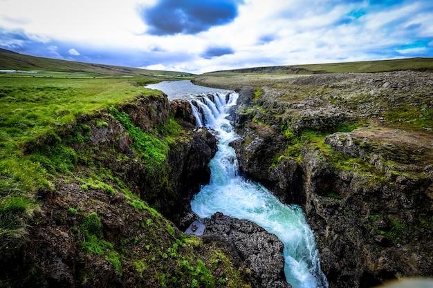 Bela foto da cachoeira que flui para baixo no meio de colinas rochosas sob um céu nublado