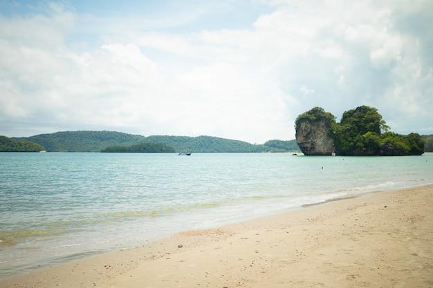 Bela foto da costa com pedras na água e montanhas ao longe