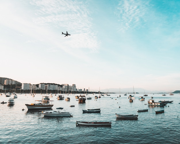 Bela foto da costa de uma cidade costeira urbana com muitos barcos e um avião voando no céu