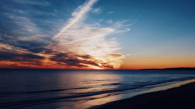 Bela foto da costa e do mar com nuvens de tirar o fôlego no céu ao amanhecer