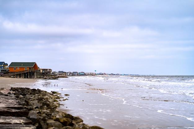 Bela foto da costa e uma casa de madeira ao longe