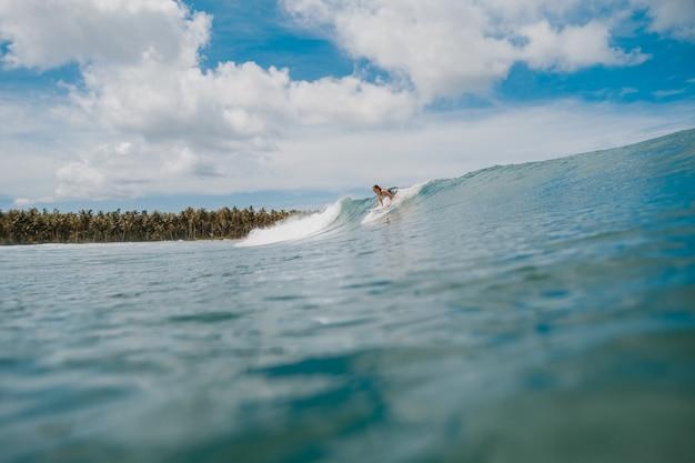 Bela foto da enorme onda quebrando do mar e do surfista na indonésia