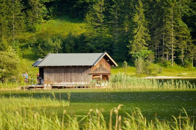 Bela foto da pequena casa de madeira entre árvores verdes e ao longo do lago