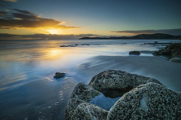 Bela foto da praia com pedra e montanha à distância sob um céu azul e amarelo