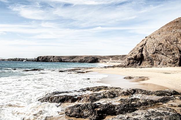 Bela foto da praia e do oceano azul em lanzarote, espanha, em um dia ensolarado